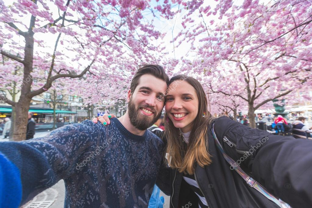 Hipster couple taking a selfie in Stockholm with cherry blossoms