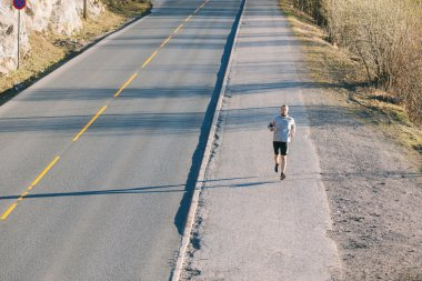 man running outside along an empty road