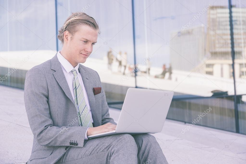 ff3bb4ff8d3b Gammaldags ung man arbetar med laptop utomhus. Han har nordiska  ansiktsdrag, och klädd i en ljus grå kostym. Det finns en modern bakgrund  med vita stenar ...