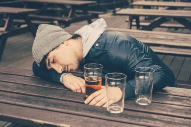 Drunk young man sleeping at pub