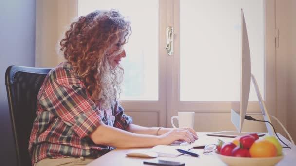 Giovane donna che lavora a casa o in un piccolo ufficio