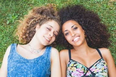 Multiracial female couple of friends lying on the grass