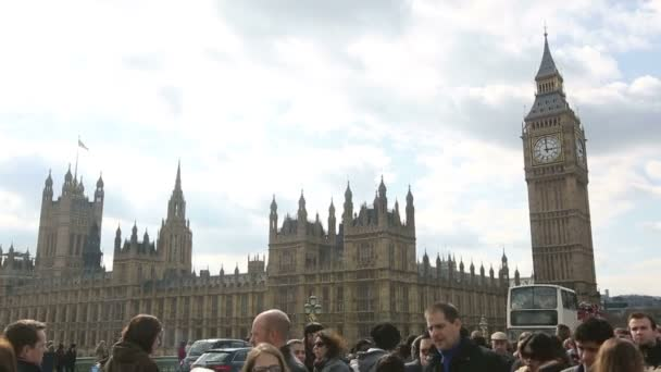 Westminster palace and Big Ben in London with lot of tourists and commuters on Westminster bridge