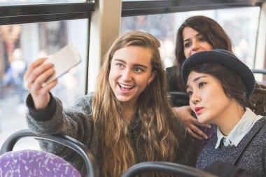 Three womentaking a selfie in the bus