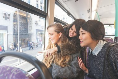 Three women looking out the window from. the bus