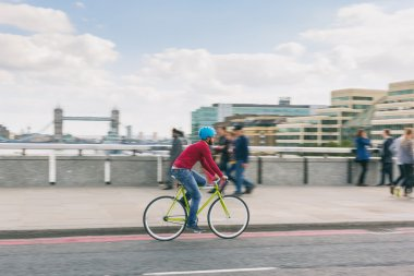 Hipster man cycling on London bridge with fixed gear bike