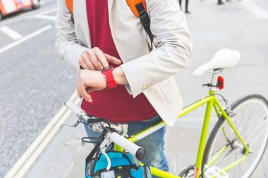 Male commuter in London looking at his smart watch