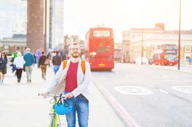 Hipster man walking on London bridge and holding his fixed gear