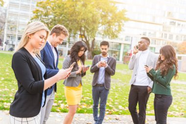 Group of people outdoor looking at their own smart phones