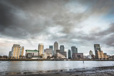 Panoramic view of London skyscrapers with a dramatic sky and clouds just before a rainstorn. Low angle view from the Thames river level. Architecture, travel and season concepts. stock vector