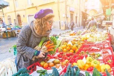 Vegetarian vegan young woman buying vegetables at local market