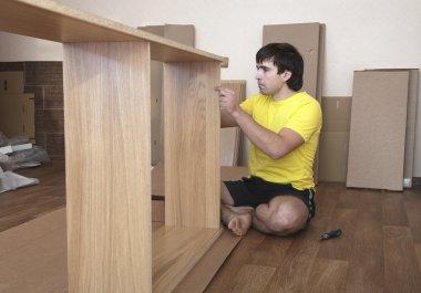 Young man assembling furniture