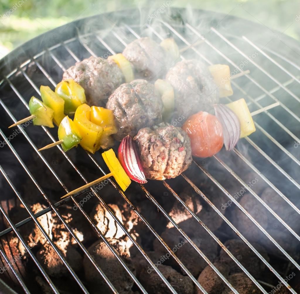 Grilled meatballs with vegetables on grill
