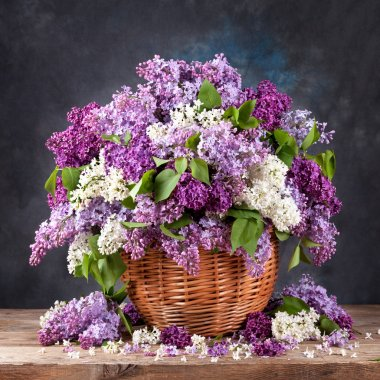 Beautiful lilacs in a basket on old boards