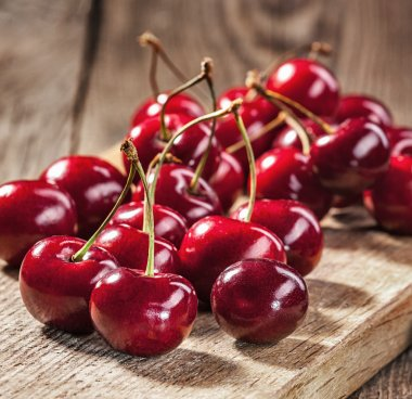 Ripe red cherries on old boards