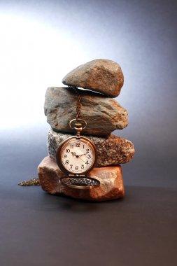 Pocket watch hanging on stones pyramid on dark background stock vector