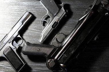 Terrorism concept. Handguns near submachine gun on dark wooden background under beam of light stock vector