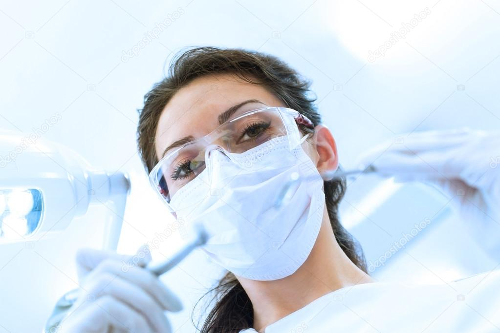 Dentist in mask holding angled mirror and drill
