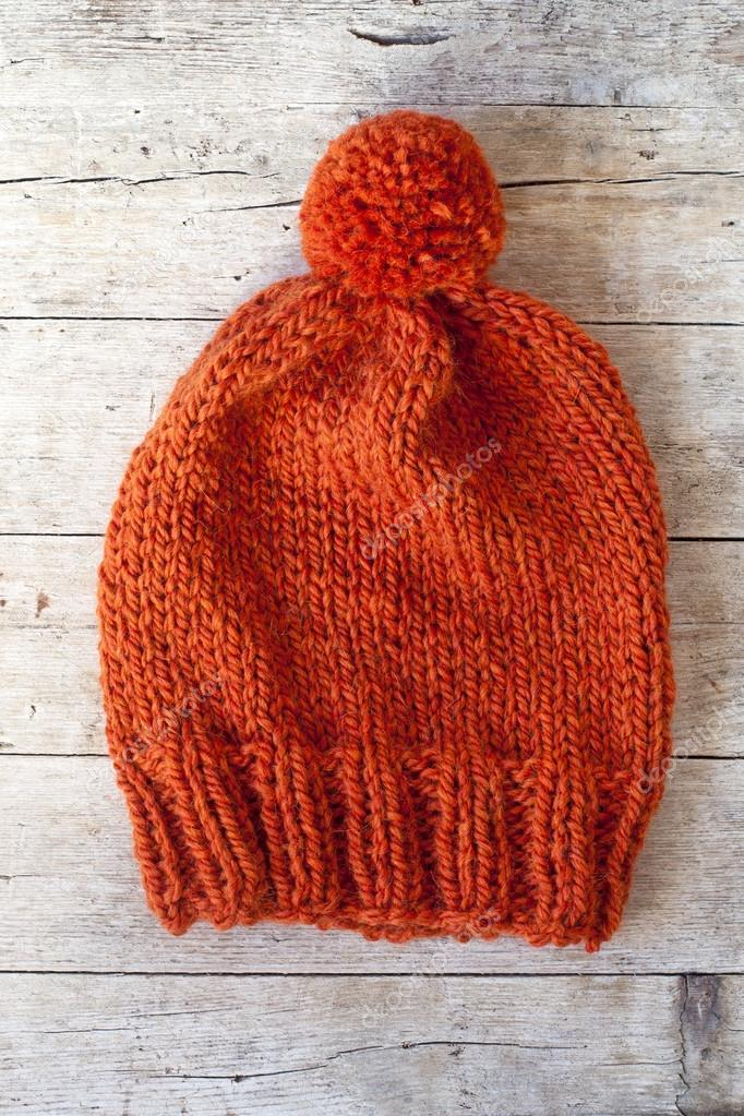 e695f3d73cc Wool orange pompom hat closeup on wooden background — Photo by ...