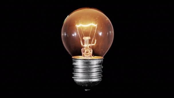 Žárovky žárovka bliká nad černou, makro, smyčky připravené
