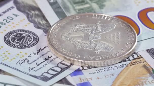 Ein-Dollar-Silbermünze amerikanischer Adler rotiert über Banknoten