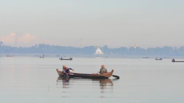 Fishermen on boat check the net