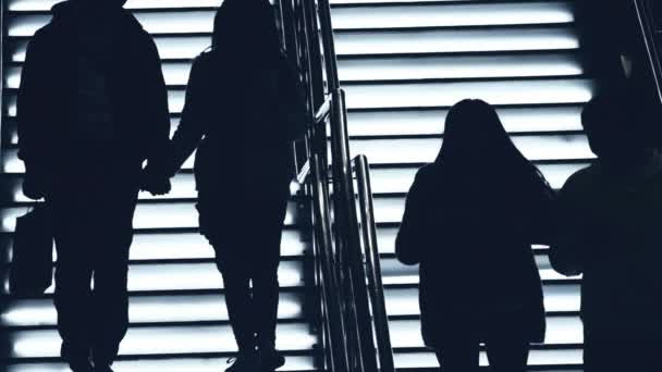 Silhouettes of young people holding hands and walking down of stairs