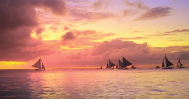 Amazing sunset sky on shore of tropical island with sail boat yachts cruising