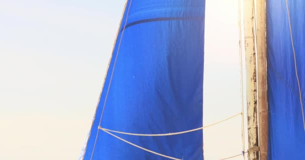 blue sail of yacht on sea coast