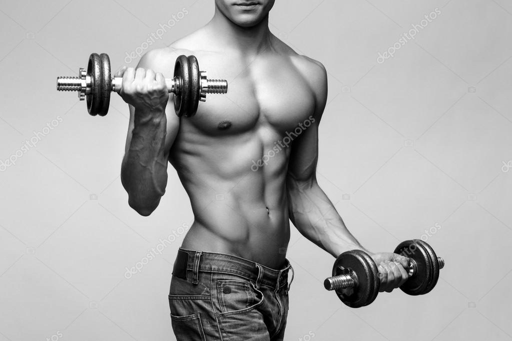 Culturista semidesnudo sosteniendo dumbell y mostrando sus brazos ...