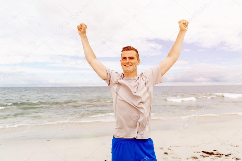 young man in sport wear with outstretched arms stock photo