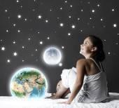 Dívka seděla v posteli a při pohledu na planetě Zemi