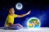 Roztomilý chlapec seděl v posteli a snění