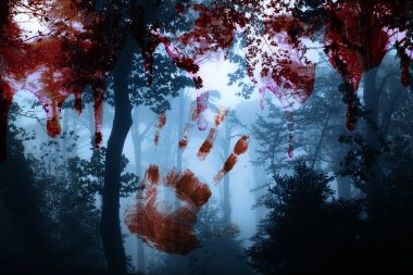 Bloody hand print and blood streaks on the background of the misty forest