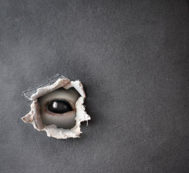 Monster eye in hole in the paper