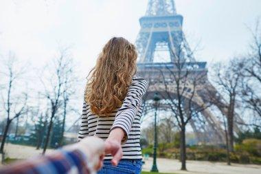 Beautiful girl near the Eiffel tower, follow me concept