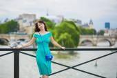 Fotografie woman in green dress on Pont des Arts in Paris, France