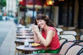 Woman drinking coffee with croissant in Parisian cafe