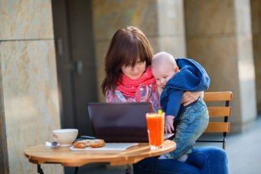 Young working mother with her son in a cafe