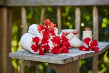 Spa setting with towels and red flowers