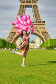 Woman near the Eiffel tower in Paris with balloons