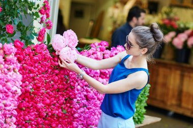 Parisian woman selecting peonies in flower shop
