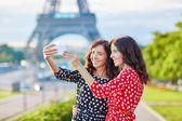 Gyönyörű ikertestvérek véve selfie, szemben az Eiffel-torony