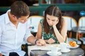 Fotografie Young romantic couple with map in French cafe