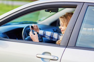 young woman driving a car and using phone