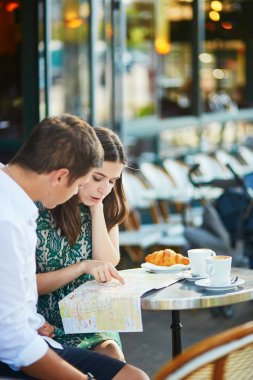Young romantic couple using map in a cozy outdoor cafe in Paris, France