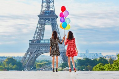 Beautiful twin sisters with colorful balloons