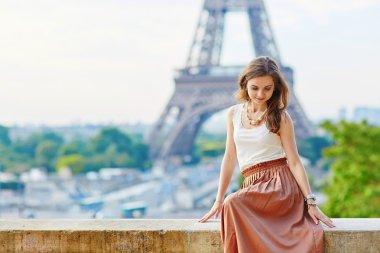 Beautiful young Parisian woman near the Eiffel tower