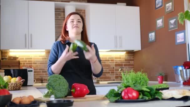 Konzept der Nahrungsmittelerlebnisse in der Hausmannskost und zu Hause. Rothaarige Frau in schwarzer Schürze jongliert in der Küche mit Zucchini, während sie gesundes Frühstück mit frischem Gemüse kocht