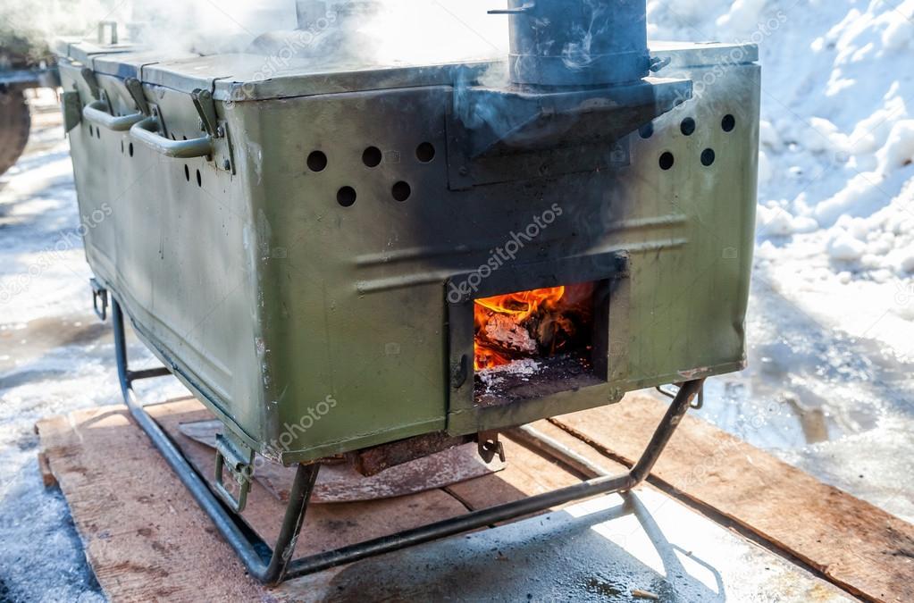 cottura di cibi su una cucina da campo militare in condizioni di